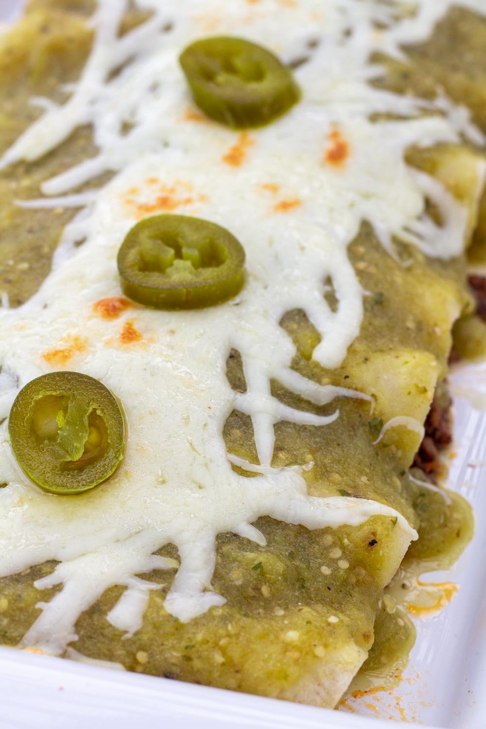 A close up of enchiladas smothered in green tomatillo sauce.