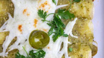 Ground beef enchiladas covered in green enchilada sauce