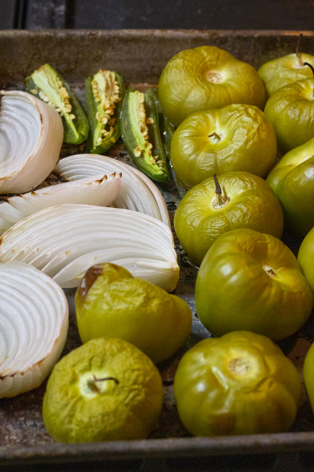 Roasted tomatillos which are wrinkly and a golden color. Onions and chiles are softened and golden.