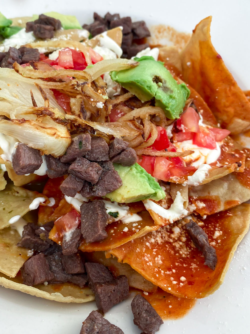 Red and green chilaquiles, smothered corn chips topped with sizzling steak, creamy sauce, and homemade red and green sauces.