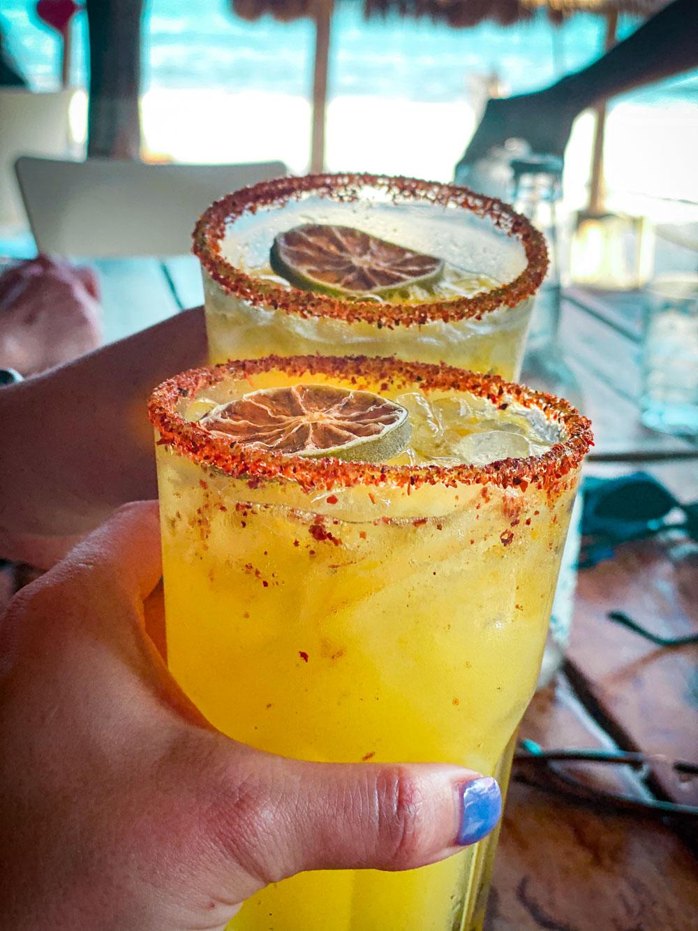2 hands cheersing passionfruit margaritas at Lido Beach Club in the Yucatan.