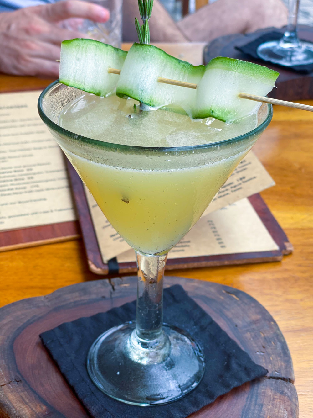 A green cocktail topped with a cucumber ribbon at a restaurant in Playa del Carmen.