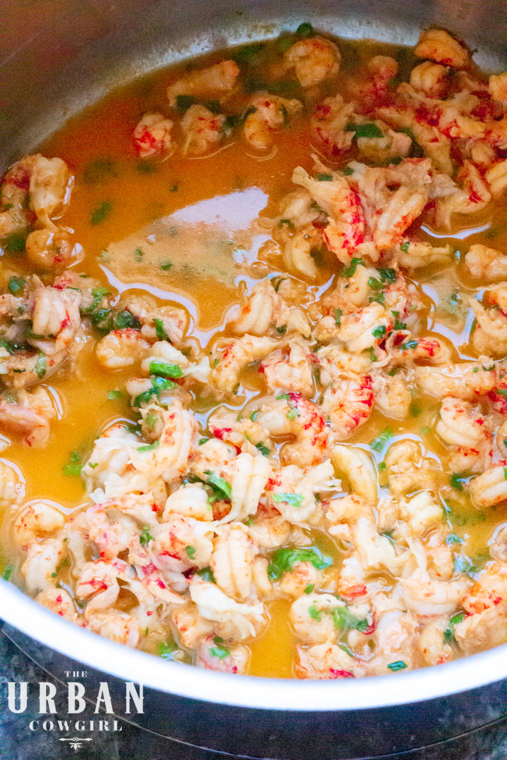 A close up of bright red poached crawfish tails in beautiful orange red butter.